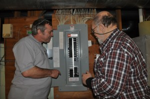Home Inspection professional, Mark Goodwin, with client inspecting breakers